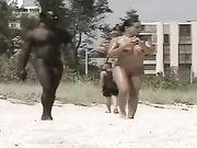 Nudo femminile con un uomo nudo nero girato in spiaggia