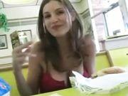 Una ragazza carina mostra tette e figa in un ristorante pubblico