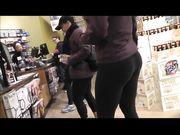 Una ragazza con un grosso culo in pantaloni di yoga è girato in negozio